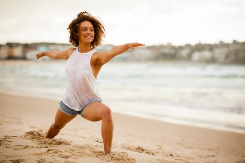 woman stretching on the beach with arms outstretched