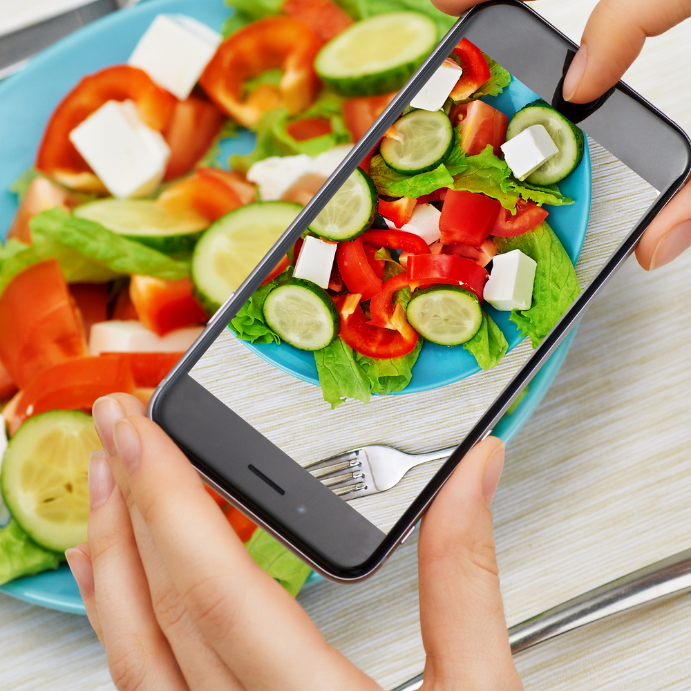 Hands holding a smartphone taking a picture of a salad