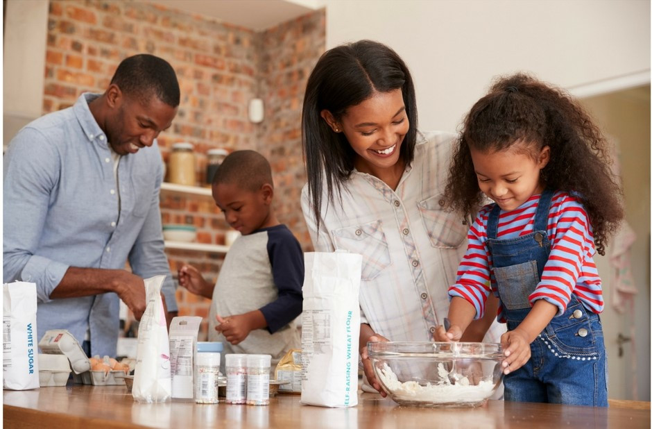 A mother and father are teaching their young son and daughter how to mix ingredients ients