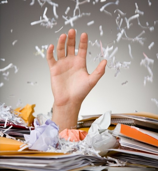 A hand is raised surrounded by piles of paperwork