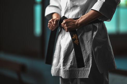 Close-up karate girl tightening  black b