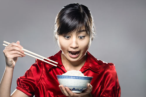 A young happy Asian girl eating rice wit