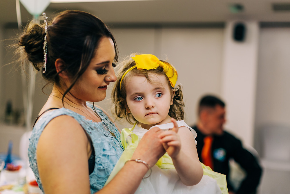 Colourful alternative wedding photography showing bridesmaid with family during reception at Holiday Inn Newcastle Jesmond