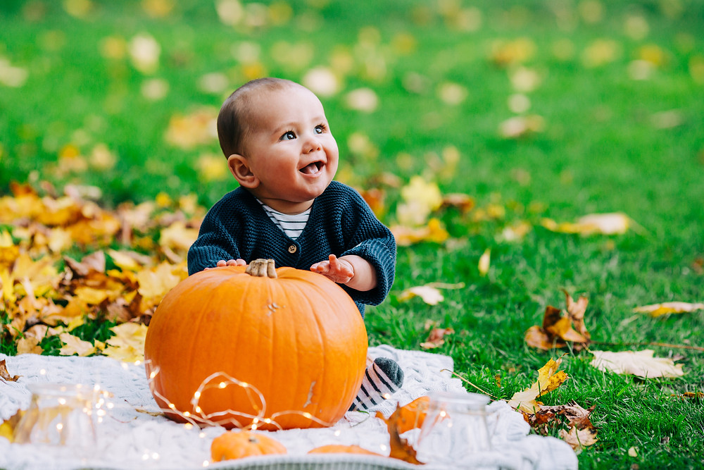 Happy cute baby laughing and sitting on blanket with pumpkin surrounded by autumn leaves in Heaton Park Newcastle