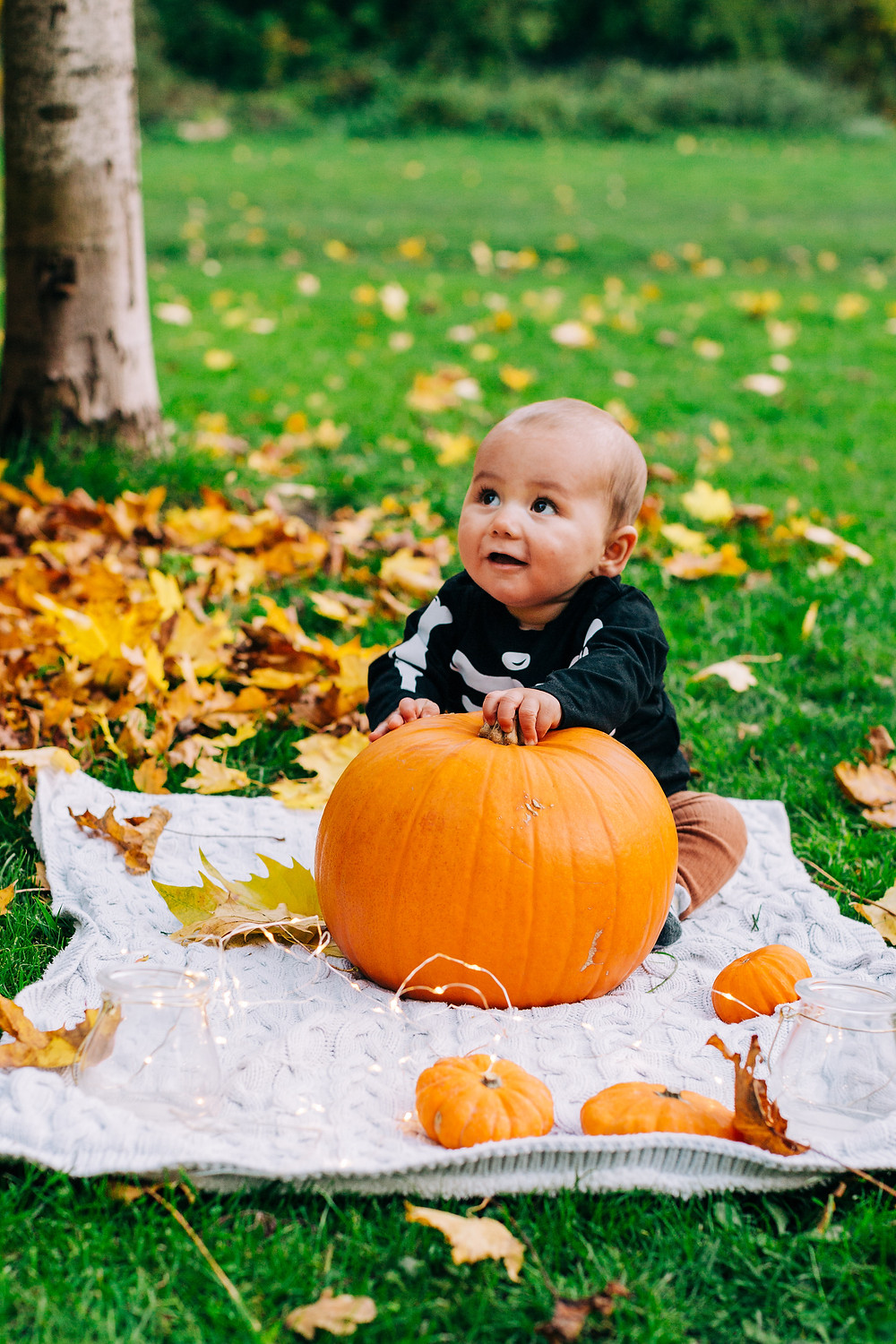 Happy baby sitting smiling with pumpkin in autumnal Heaton Park, Newcastle
