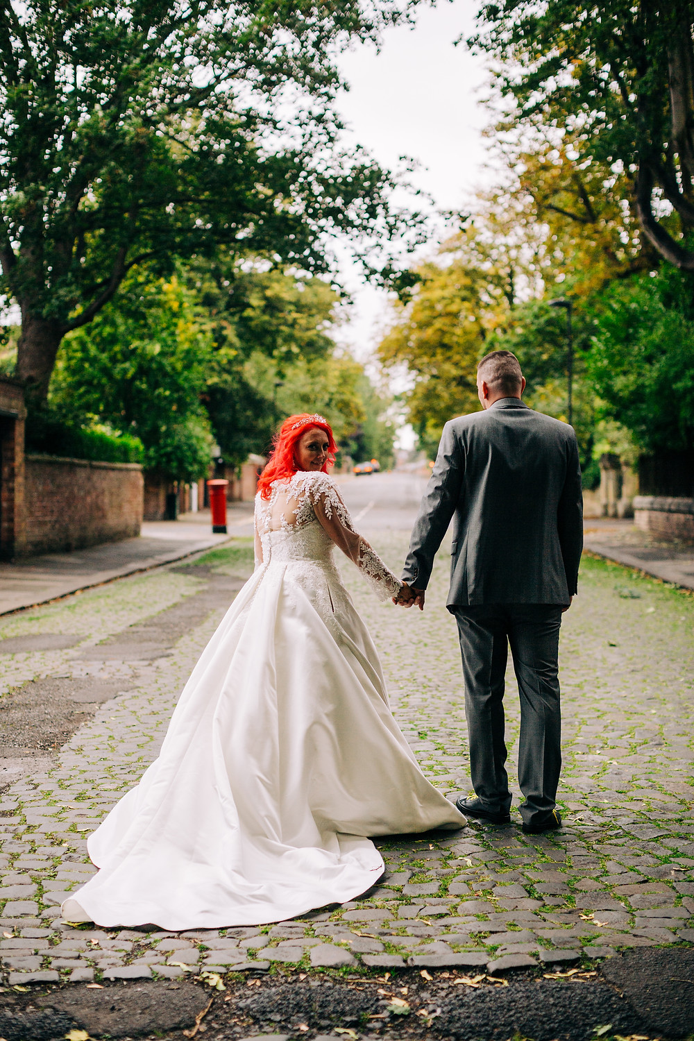 Colourful alternative wedding photography showing bride and groom during portrait session on cobbled leafy street near Holiday Inn Newcastle Jesmond