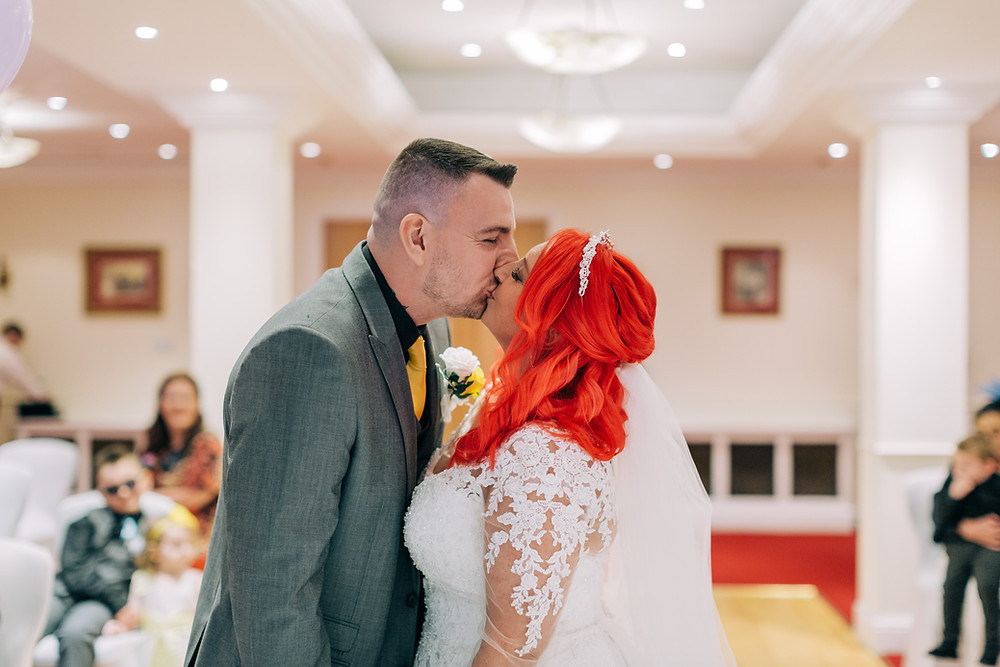 Colourful documentary style wedding photography showing couple kiss during ceremony Holiday Inn Newcastle Jesmond