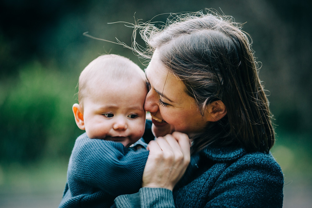 Mum cuddling baby and laughing in autumnal Heaton Park, Newcastle family and baby photographer