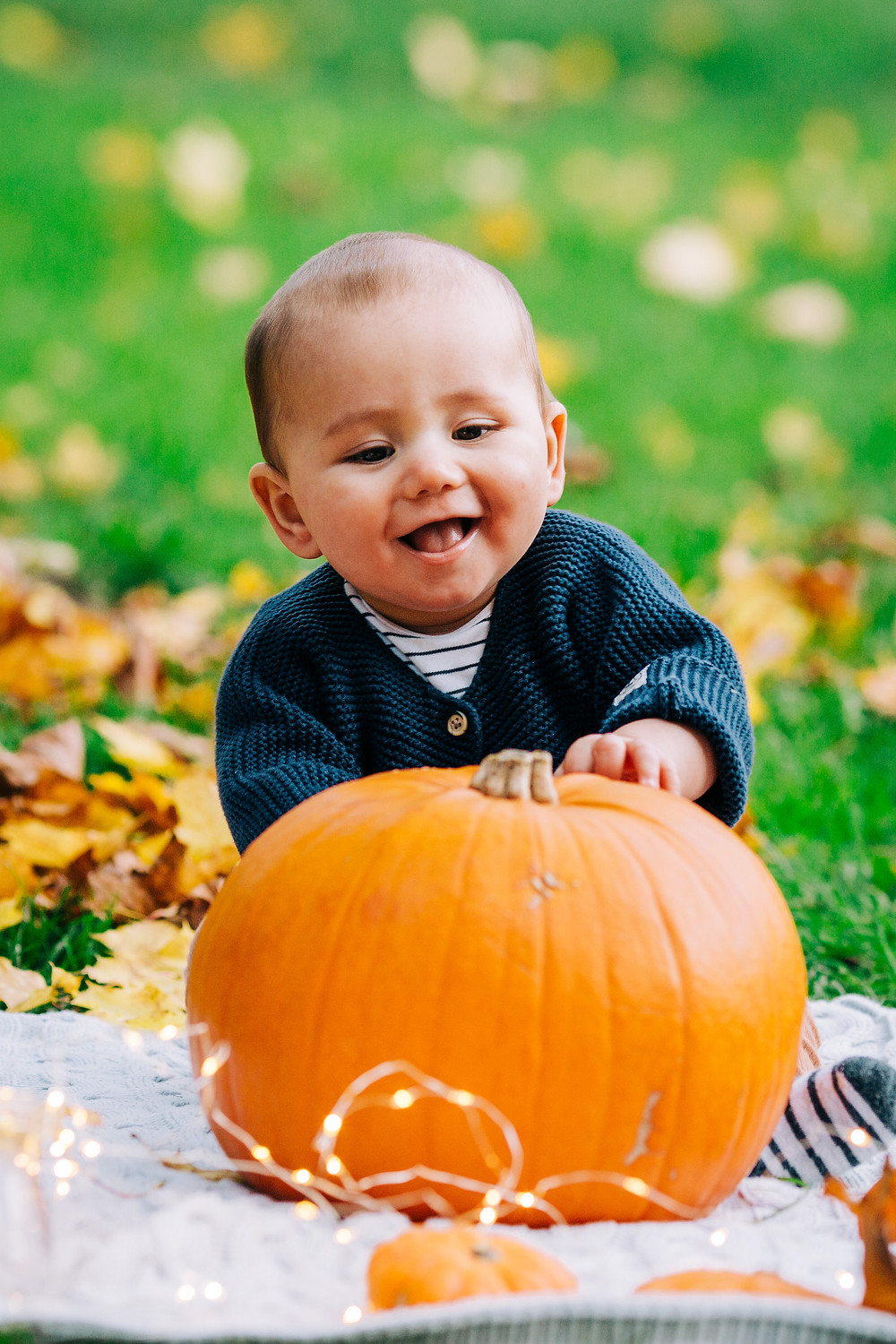 Autumnal baby photography, happy cute baby sitting with pumpkin in Heaton Park Newcastle