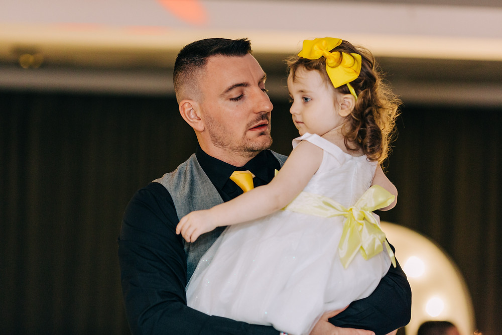 Colourful alternative wedding photography showing groom with daughter during reception at Holiday Inn Newcastle Jesmond