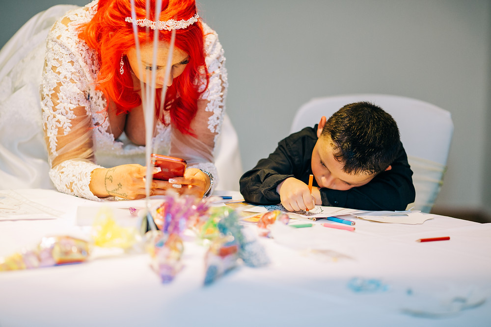 Colourful wedding photography showing bride colouring with kids at reception Holiday Inn Newcastle