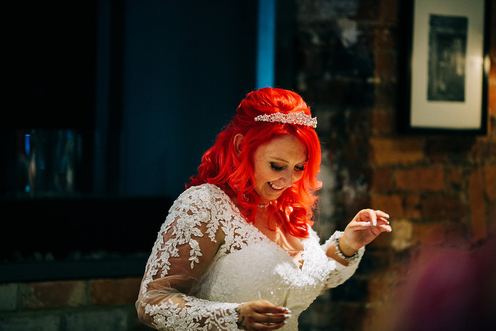 Colourful alternative wedding photography showing bride having fun after ceremony at Holiday Inn Newcastle Jesmond