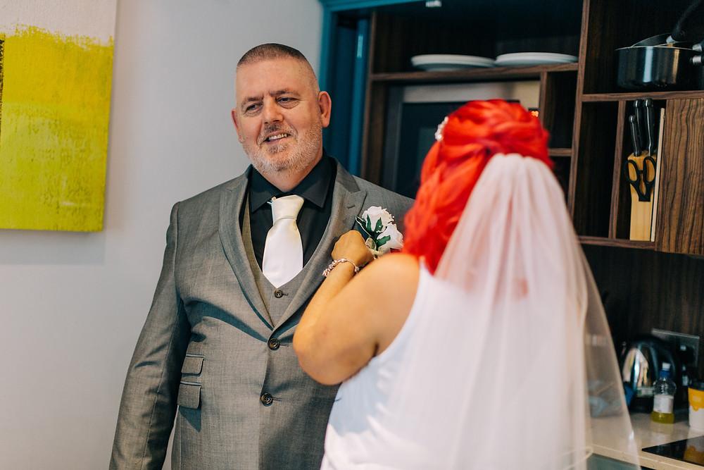 Colourful documentary style wedding photo of bride helping father of the bride get ready at Holiday Inn Jesmond Newcastle