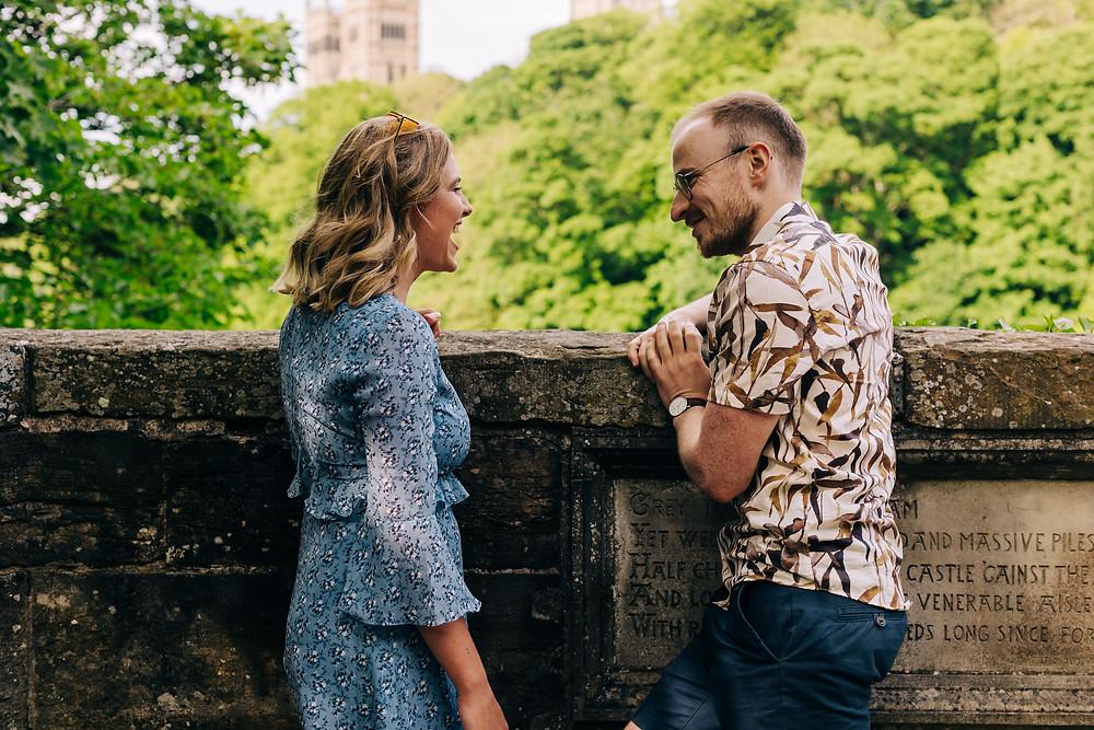 Couple laughing on bridge engagement shoot Durham city