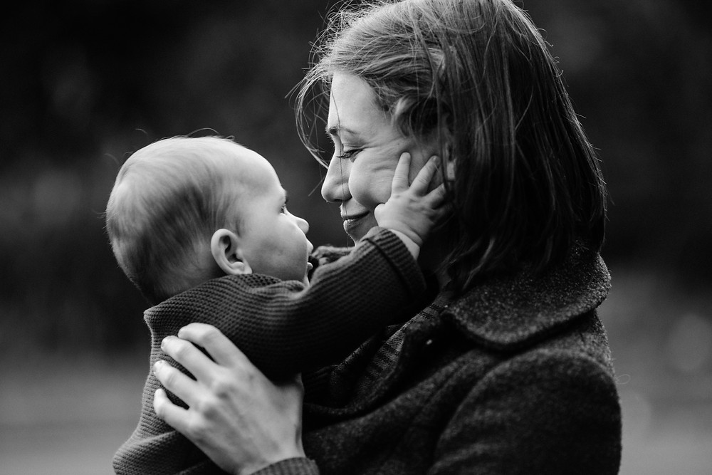 Black and white family photographer, mother holding baby in autumnal Heaton Park, Newcastle