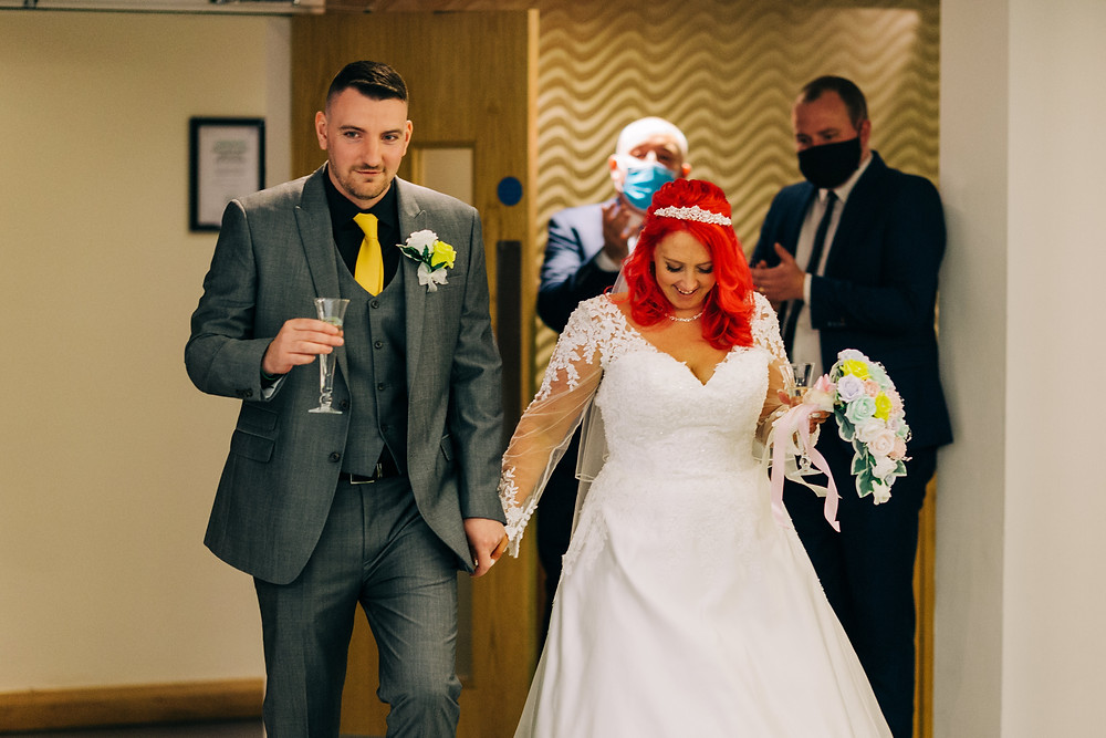 Colourful documentary style wedding photography showing couple's entrance after ceremony Holiday Inn Newcastle Jesmond