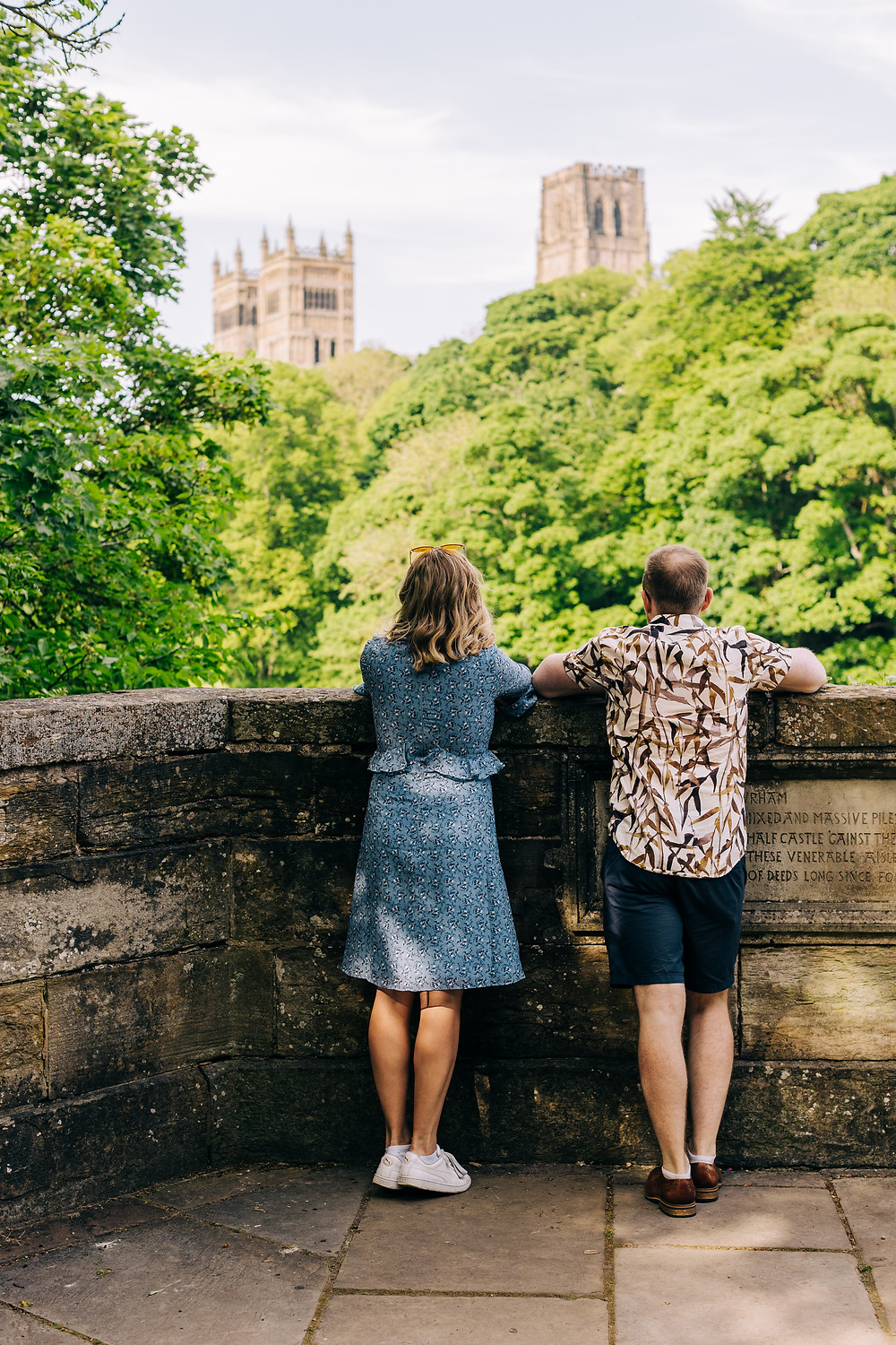 Couple looking at Durham cathedral romantic casual engagement shoot in the city