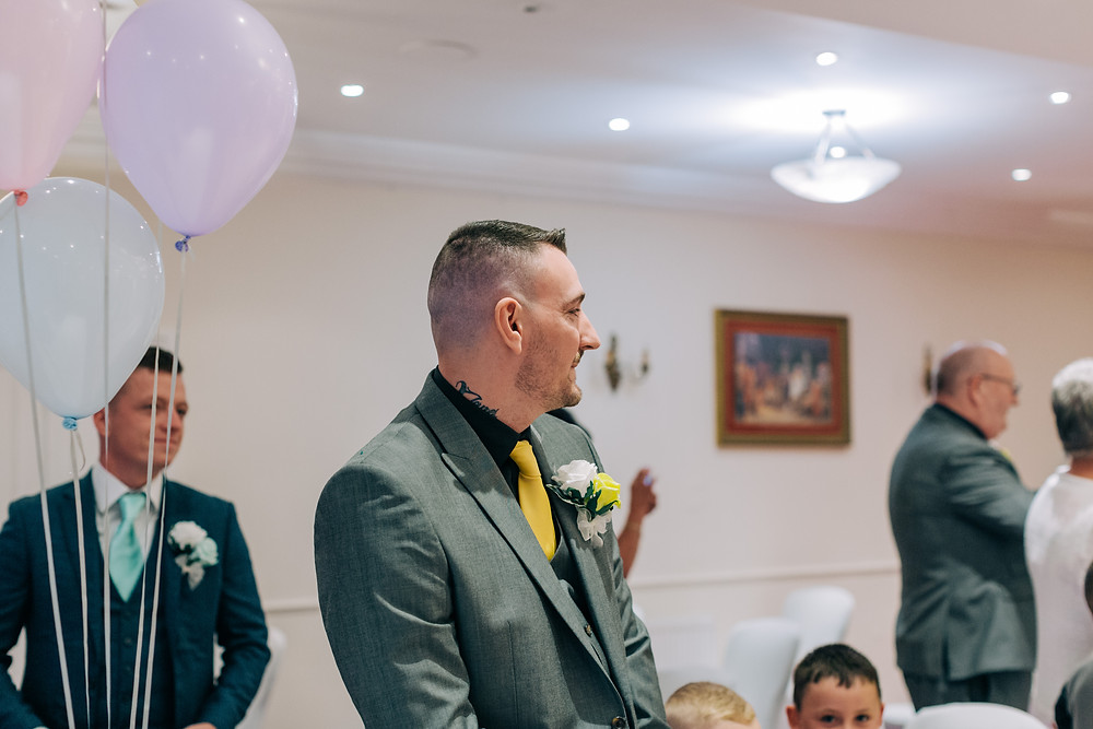 Colourful documentary style wedding photography showing groom waiting for bride at Holiday Inn Jesmond Newcastle ceremony