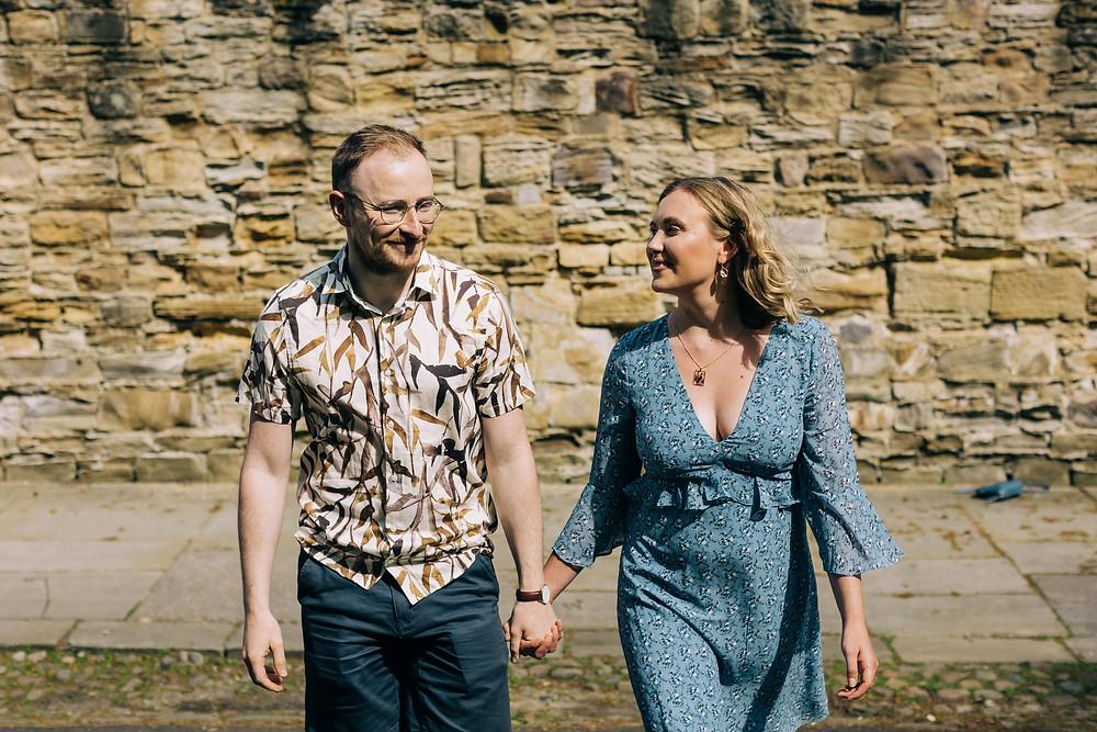Romantic couple walking through Durham pre wedding shoot sunny