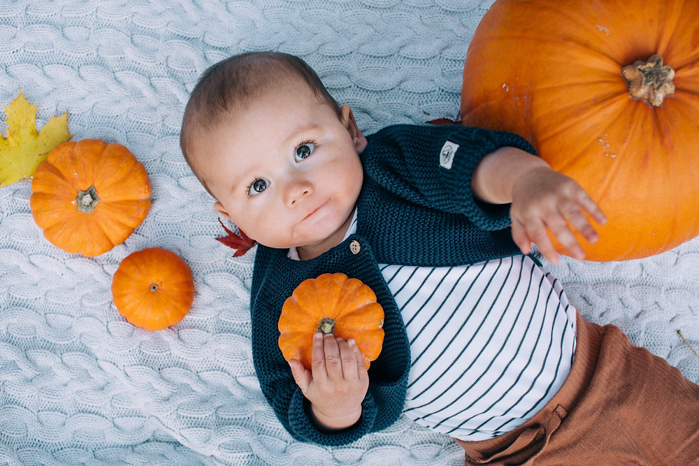 Baby lying on blanket surrounded by pumpkins and autumn objects in Heaton Park, Newcastle, baby and family photography