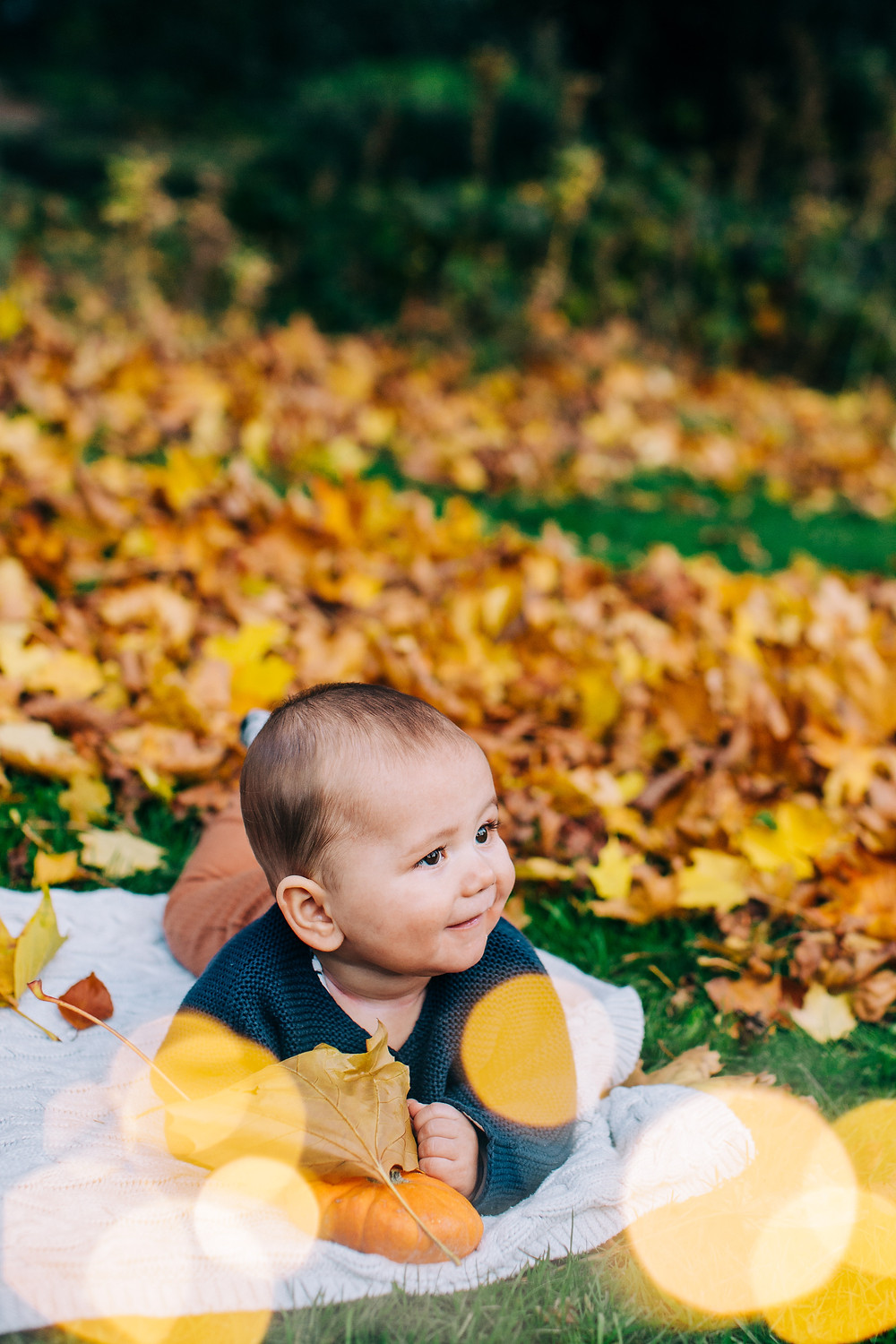 Photograph of baby lying on blanket in autumnal Heaton Park, Newcastle