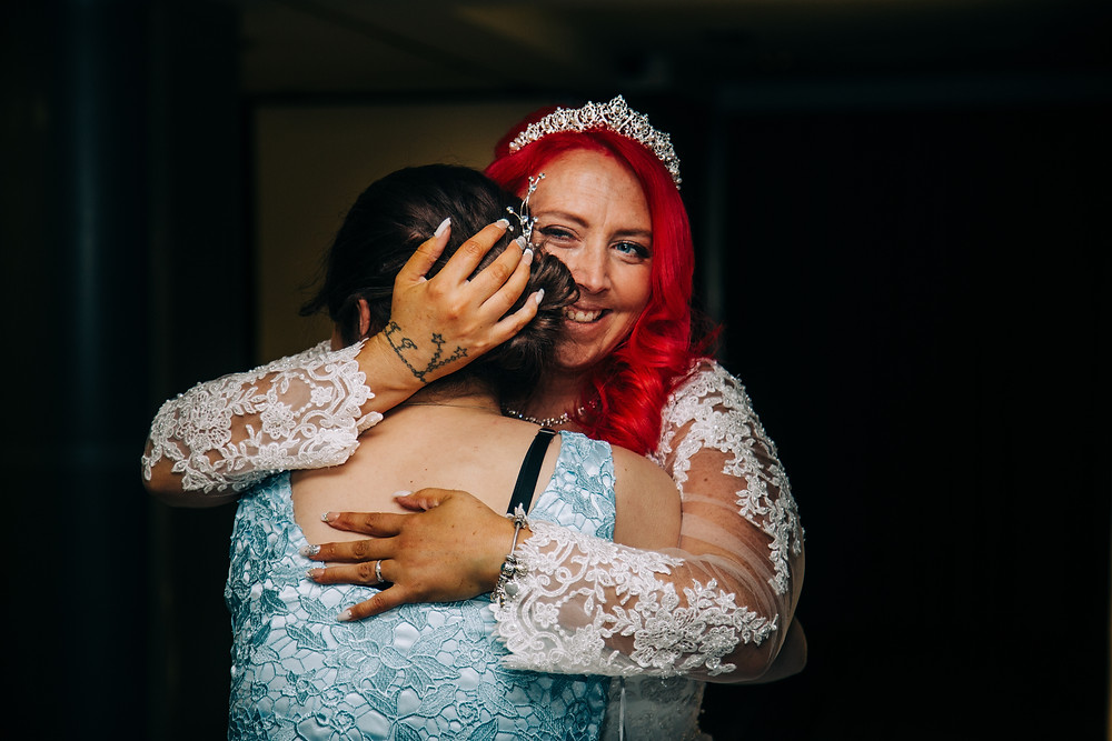 Colourful alternative wedding photography showing bride hugging bridesmaid after ceremony at Holiday Inn Jesmond Newcastle