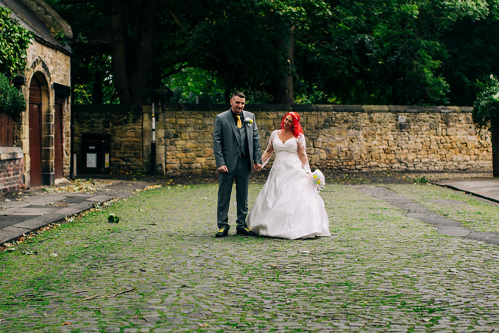 Colourful alternative wedding photography showing bride and groom during portrait session in leafy cobbled street near Holiday Inn Newcastle Jesmond