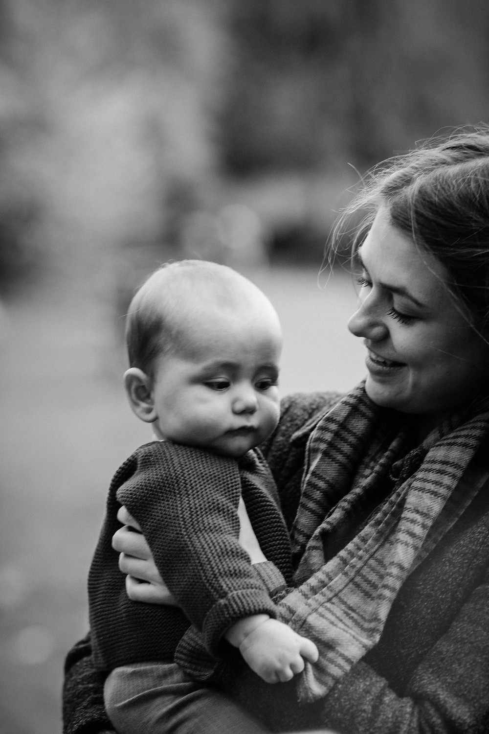 Black and white image of mother and baby in autumnal Heaton Park, Newcastle