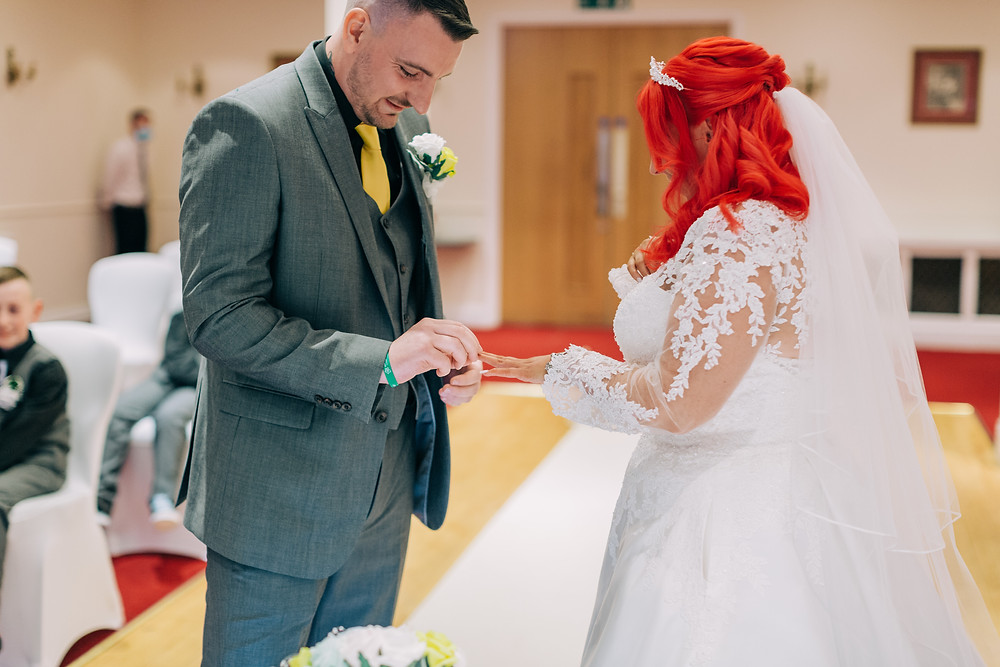 Colourful documentary style wedding photography showing ring exchange during ceremony Holiday Inn Newcastle Jesmond