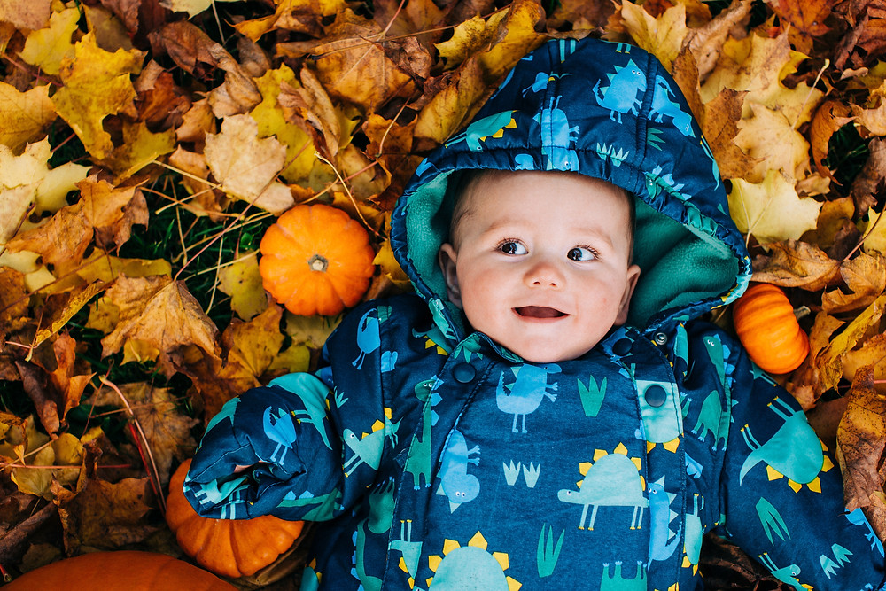 happy baby lying in autumn leaves, surrounded by pumpkins, in Heaton Park, Newcastle family and baby photographer