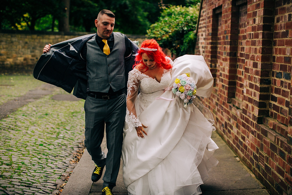 Colourful alternative wedding photography showing groom giving bride his jacket on leafy street during portrait session near Holiday Inn Newcastle Jesmond