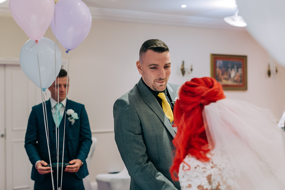 Colourful documentary style wedding photography showing couple during ceremony Holiday Inn Newcastle Jesmond