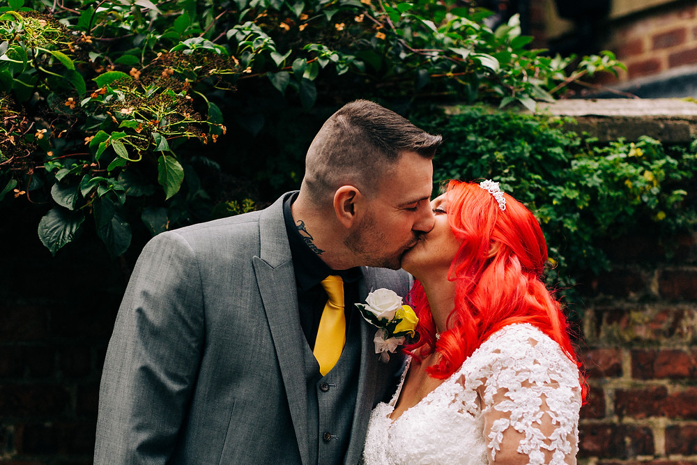 Colourful alternative wedding photography showing bride and groom on leafy street during portrait session near Holiday Inn Newcastle Jesmond