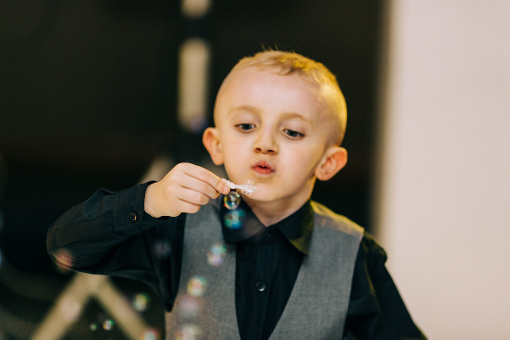 Colourful wedding photography showing son blowing bubbles at reception Holiday Inn Newcastle