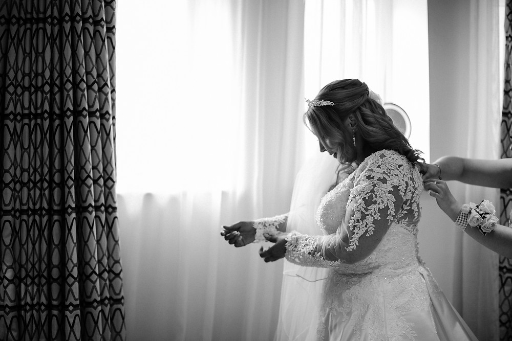 Black and white documentary wedding style photography showing bridesmaid helping bride get ready at Holiday Inn Newcastle Jesmond