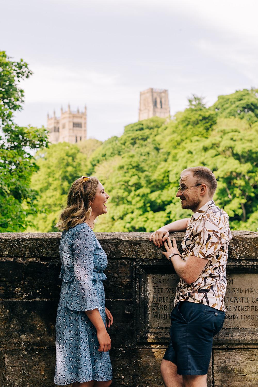 Couple laughing on bridge Durham university cathedral engagement shoot