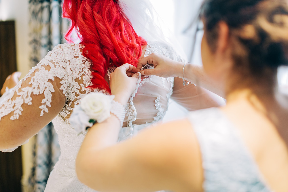 Colourful documentary wedding style photography showing detail of bridesmaid helping bride get ready at Holiday Inn Newcastle Jesmond