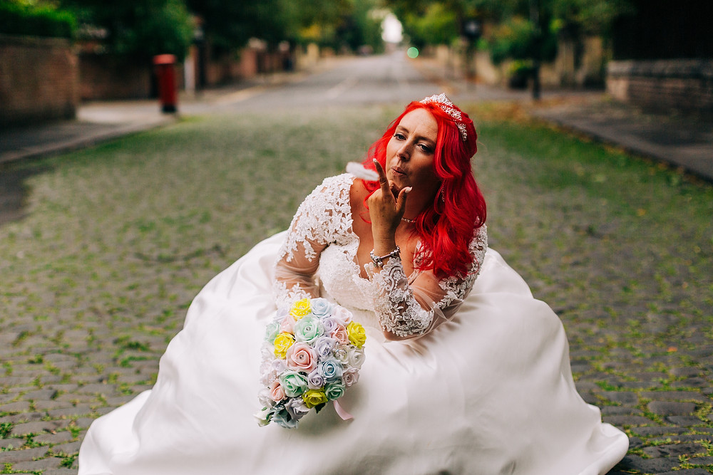 Colourful alternative wedding photography showing bride during portrait session in leafy cobbled street near Holiday Inn Newcastle Jesmond