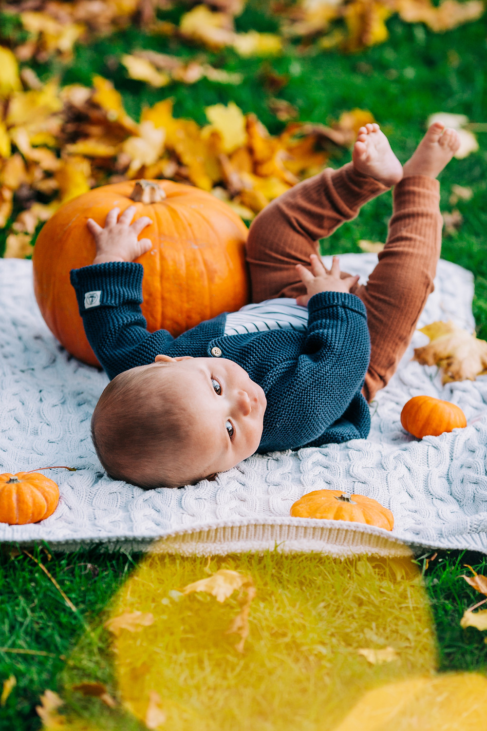 Baby lying on blanket, surrounded by pumpkins and autumnal leaves in Heaton Park, Newcastle