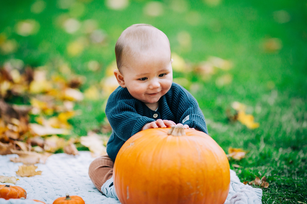 Happy smiling baby playing with pumpkins sitting on blanket in autumnal Heaton Park, Newcastle family and baby photographer