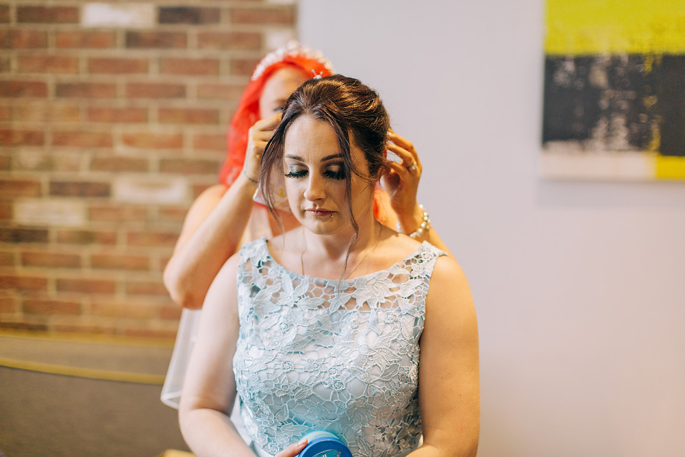 Colourful documentary style photo of bride helping bridesmaid get ready at Holiday Inn Newcaslte