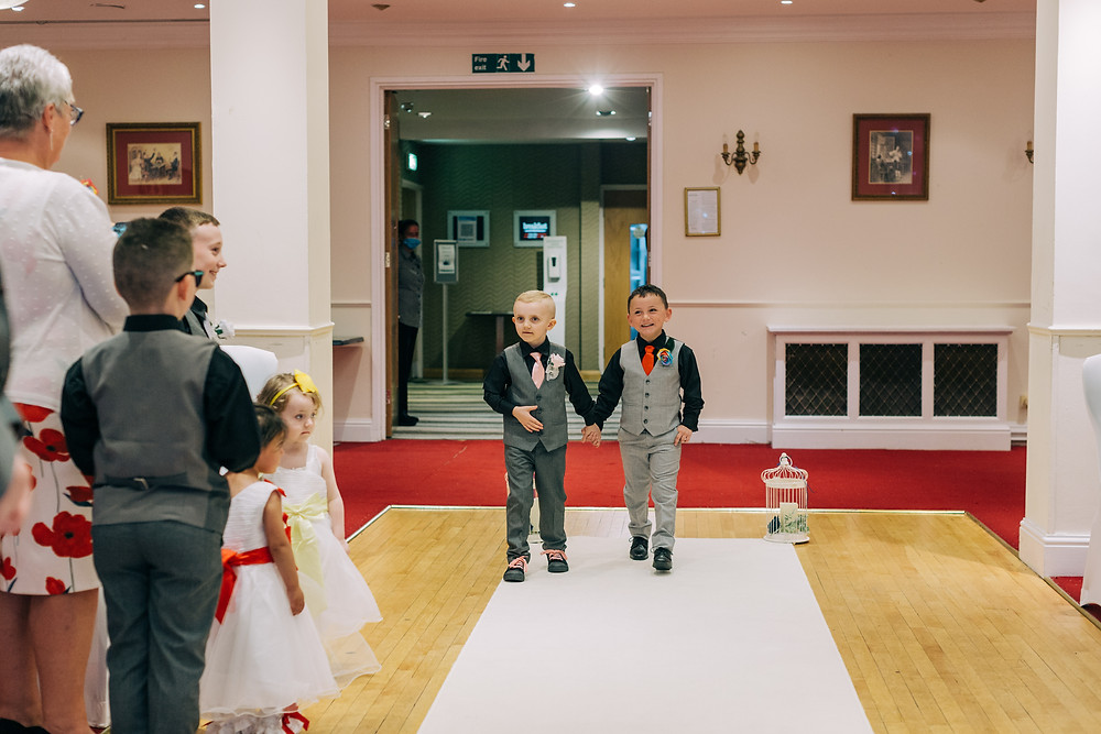 Colourful documentary style wedding photography showing family walking down the aisle at Holiday Inn Jesmond Newcastle