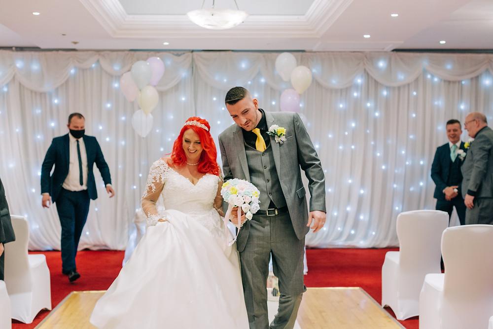 Colourful documentary style wedding photography showing couple leaving ceremony Holiday Inn Newcastle Jesmond