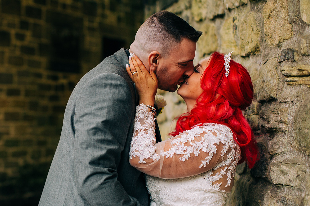 Colourful alternative wedding photography showing bride and groom during portrait session next to stone wall near Holiday Inn Newcastle Jesmond