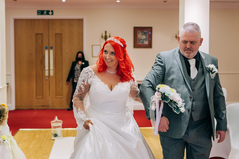 Colourful documentary style wedding photography showing bride walking down aisle at Holiday Inn Newcastle Jesmond