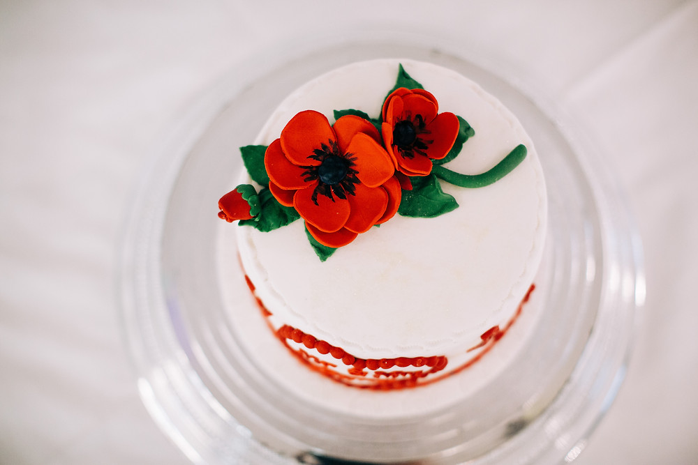 Colourful alternative wedding photography showing wedding cake with poppies at Holiday Inn Newcastle Jesmond
