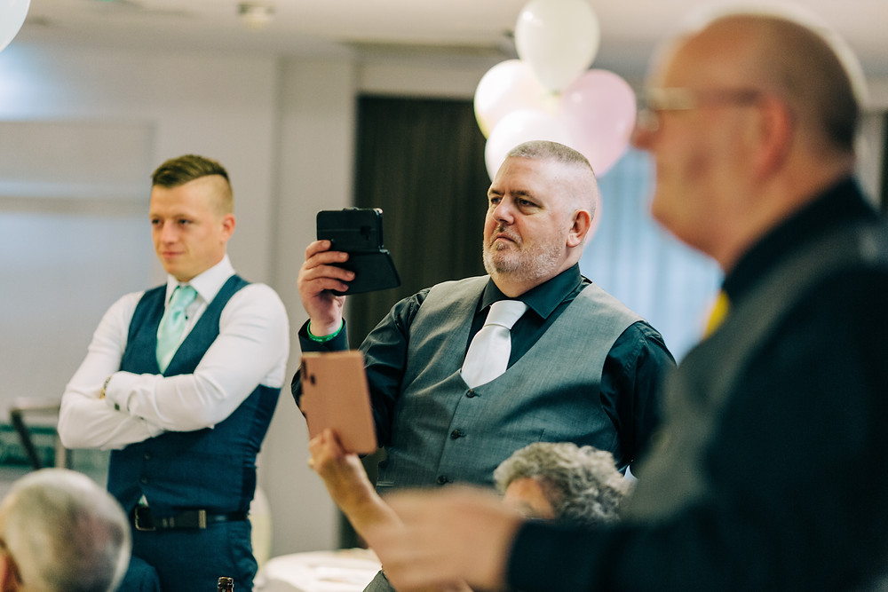Colourful alternative wedding photography showing family during dedication at Holiday Inn Newcastle Jesmond