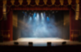 An empty stage of the theater, lit by sp