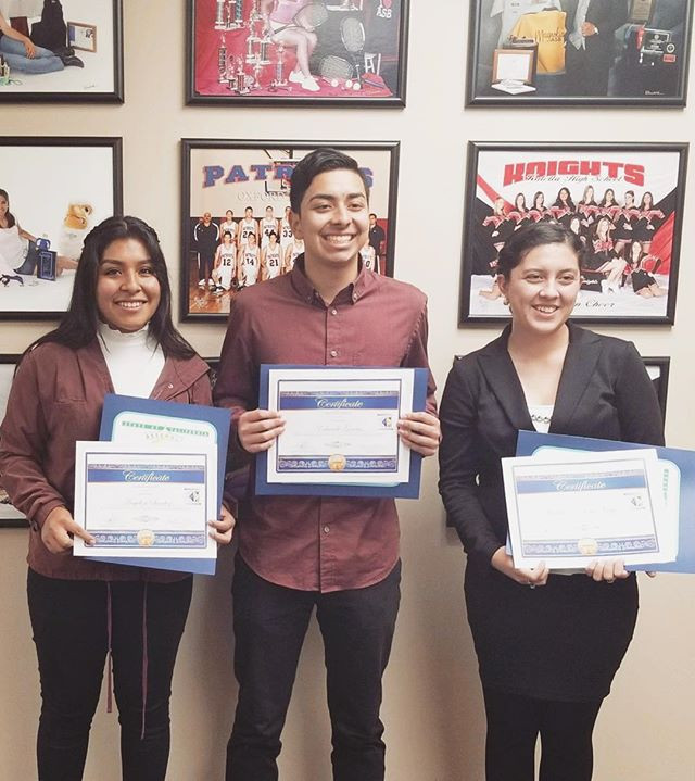 3 high school students stand proudly holding their awards presented by their school district board of trustees