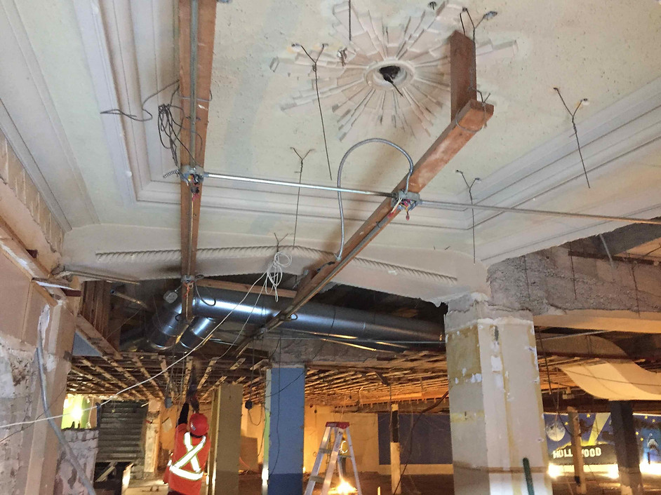 August 28, 2019:  Facing east, some of the decorative plaster framing and drop ceiling can be seen here. A worker is removing some of the wooden ceiling framing in the photo.